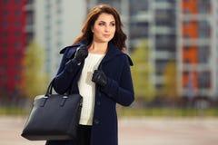 Happy young fashion woman with handbag walking on city street Royalty Free Stock Photo
