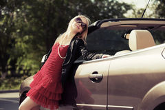 Happy young fashion woman leaning on convertible car Royalty Free Stock Images