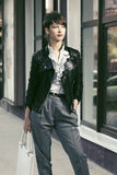 Happy young fashion woman in leather jacket with handbag in a city street Royalty Free Stock Image