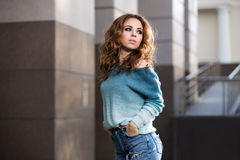 Happy young fashion woman with long curly hairs on city street Stock Photos