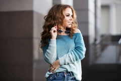 Happy young fashion woman with long curly hairs on city street Royalty Free Stock Photography