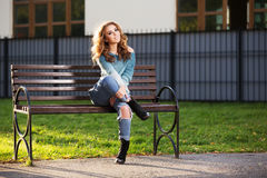 Happy young fashion woman with long curly hairs sitting on bench Royalty Free Stock Photo