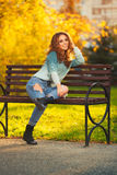 Happy young fashion woman with long curly hairs sitting on bench Stock Photo