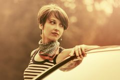 Happy young fashion woman with pixie hair leaning on her car royalty free stock photo