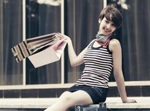 Happy young fashion woman with shopping bag sitting on mall steps Royalty Free Stock Photos