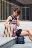 Happy young fashion woman with shopping bags calling on phone Royalty Free Stock Photo