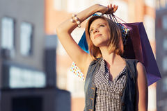 Happy young fashion woman with shopping bags on city street Royalty Free Stock Photo