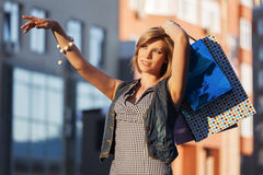 Happy young fashion woman with shopping bags on city street Stock Photos