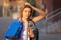 Happy young fashion woman with shopping bags on city street Royalty Free Stock Photos