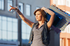 Happy young fashion woman with shopping bags on the city street Royalty Free Stock Images