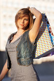Happy young fashion woman with shopping bags on a city street Stock Photography