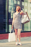 Happy young fashion woman with shopping bags on city street Royalty Free Stock Photography