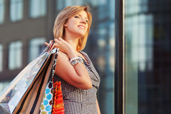 Happy young fashion woman with shopping bags in the mall Stock Image