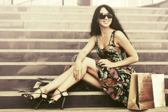 Happy young fashion woman with shopping bags on mall steps Royalty Free Stock Image
