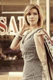 Happy young fashion woman with shopping bags in the mall Royalty Free Stock Photo