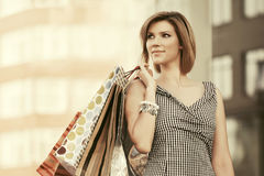 Happy young fashion woman with shopping bags at the mall Stock Photography