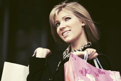Happy young fashion woman with shopping bags in the mall Stock Photography