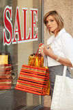 Happy young fashion woman with shopping bags at the mall window Royalty Free Stock Images