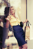 Happy young fashion woman with shopping bags at the mall window Royalty Free Stock Photo
