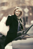 Happy young fashion woman with shopping bags next to her car Royalty Free Stock Photography