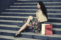 Happy young fashion woman with shopping bags sitting on mall steps Royalty Free Stock Images