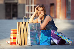 Happy young fashion woman with shopping bags sitting on sidewalk Stock Photography