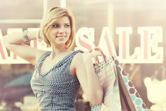 Happy young fashion woman with shopping bags walking in the mall Stock Photography