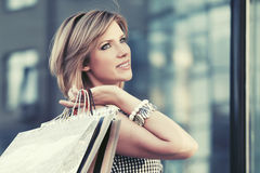 Happy young fashion woman with shopping bags walking in the mall Royalty Free Stock Images