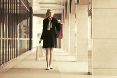 Happy young fashion woman with shopping bags in the mall. Happy young fashion woman with shopping bags walking in the mall Royalty Free Stock Image