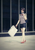 Happy young fashion woman with shopping bags walking next to mall Stock Images