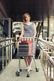 Happy young fashion woman with shopping cart Royalty Free Stock Image