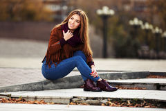 Happy young fashion woman sitting on city street Stock Image