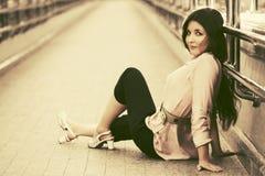 Happy young fashion woman sitting on sidewalk Stock Image