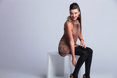 Happy young fashion woman sitting on a white chair Royalty Free Stock Photography