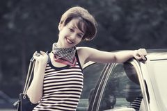 Happy young fashion woman in striped tank top leaning on her car. Happy young fashion woman wearing striped tank top and silk scarf leaning on her car stock images