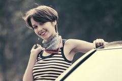 Happy young fashion woman in striped tank top leaning on her car Royalty Free Stock Image