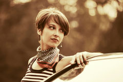 Happy young fashion woman in tank top next to her car Royalty Free Stock Photos