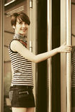 Happy young fashion woman in tank top next to mall door royalty free stock photos