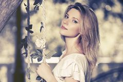 Happy young fashion woman wearing white top in city park. Happy young fashion blond woman wearing white top in city park stock photo