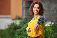 Happy young fashion woman in yellow shirt with bouquet of flowers royalty free stock photo