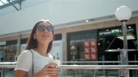 Happy young fashionable woman taking a coffee break after shopping, smiling with a coffee-to-go in her hands against stock video footage