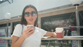 Happy young fashionable woman taking a coffee break after shopping, smiling with a coffee-to-go in her hands against stock video