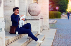 Happy young father busy with work with his newborn son Stock Image