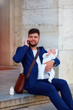 Happy young father busy with work with his newborn son Stock Photos