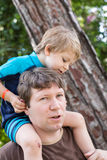 Happy Young father giving little boy a ride on shoulders Royalty Free Stock Image