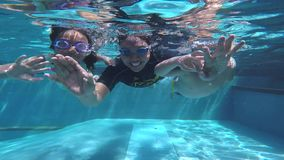 Father and children diving together in pool stock footage