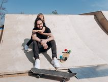 Happy young father and his son dressed in the stylish casual clothes are sitting in an embrace together on the slide royalty free stock image