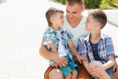 Happy young father with his two sons. Happy young father,a brunette with short hair, spends time on the street in the summer with his two sons,boys 5-7 years old Stock Photography