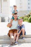 Happy young father with his two sons. Happy young father,a brunette with short hair, spends time on the street in the summer with his two sons,boys 5-7 years old Stock Photos