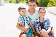 Happy young father with his two sons. Happy young father,a brunette with short hair, spends time on the street in the summer with his two sons,boys 5-7 years old Stock Photo